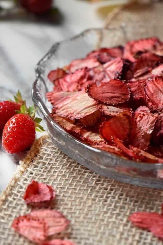 Oven dried strawberries, in a round glass dish, surrounded by a few fresh strawberries.