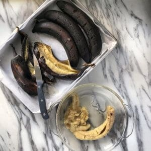 A few black bananas have been slit open with a knife. The interior of the roasted bananas are placed in a bowl.