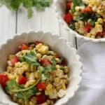 A close up shot of a white bowl filled with sweet corn salad.