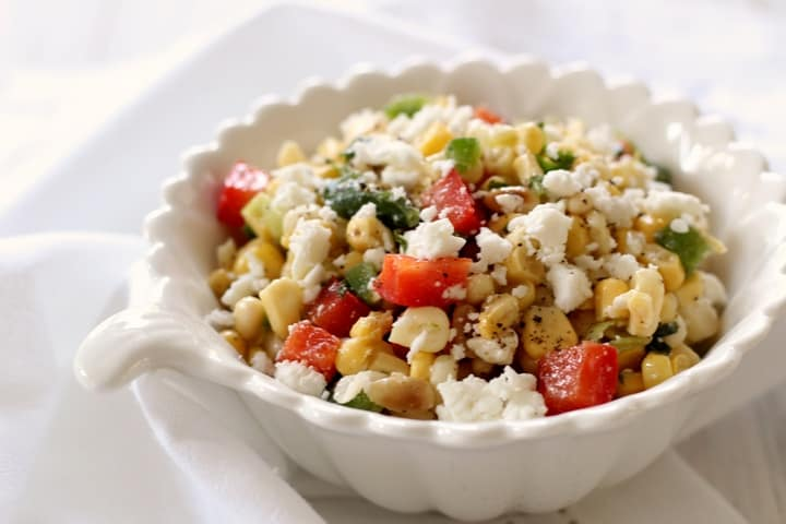 A white serving bowl of sweet corn salad sprinkled with feta cheese.