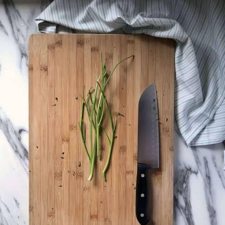 Parsley stalks without the leaves, on a cutting board.