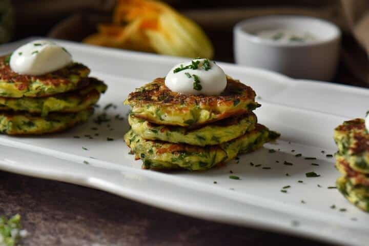 Italian zucchini fritters are stacked in groups of threes and are topped with a dollop of yogurt and sprinkled with chives.