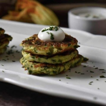 A stack of three zucchini cakes topped with yogurt on a white serving dish,