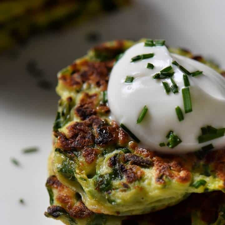 A close up of the crisp edges of a zucchini fritter served with a dollop of yogurt sauce.
