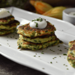 A stack of three zucchini fritters with a dollop of yogurt sauce.