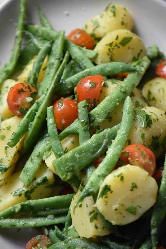 A close up shot of bright green string beans, red cherry tomatoes and creamy new potatoes.