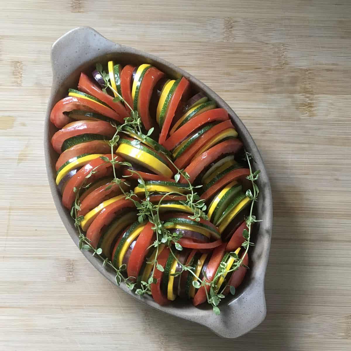 Sliced tomatoes, zucchini and eggplant in a casserole dish.