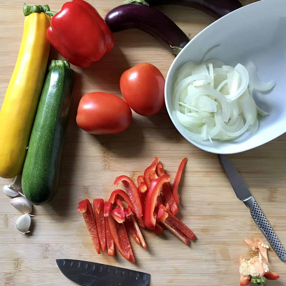 A sliced red pepper on a cutting board, surrounded by other vegetables.