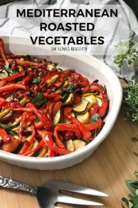 A white casserole dish with oven roasted peppers, zucchini and eggplant.