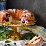 Lemon Blueberry Cake on a cake stand next to a slice of blueberry cake.