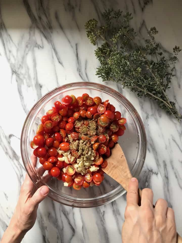 Sliced garlic and dried oregano in the process of being mixed with the sliced cherry tomatoes.