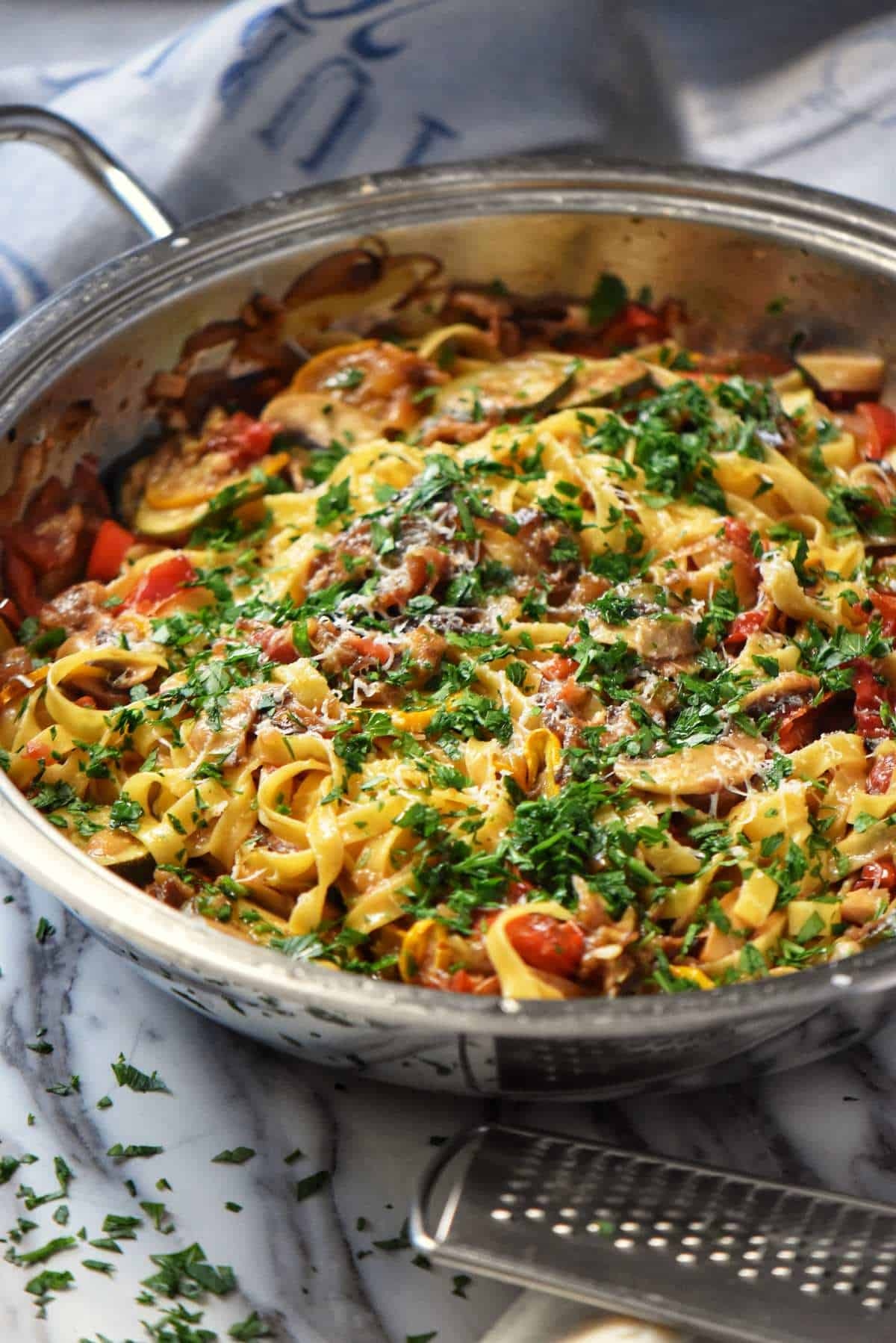 Roasted Vegetable Pasta combined together in a pan, with a sprinkle of minced Italian parsley.