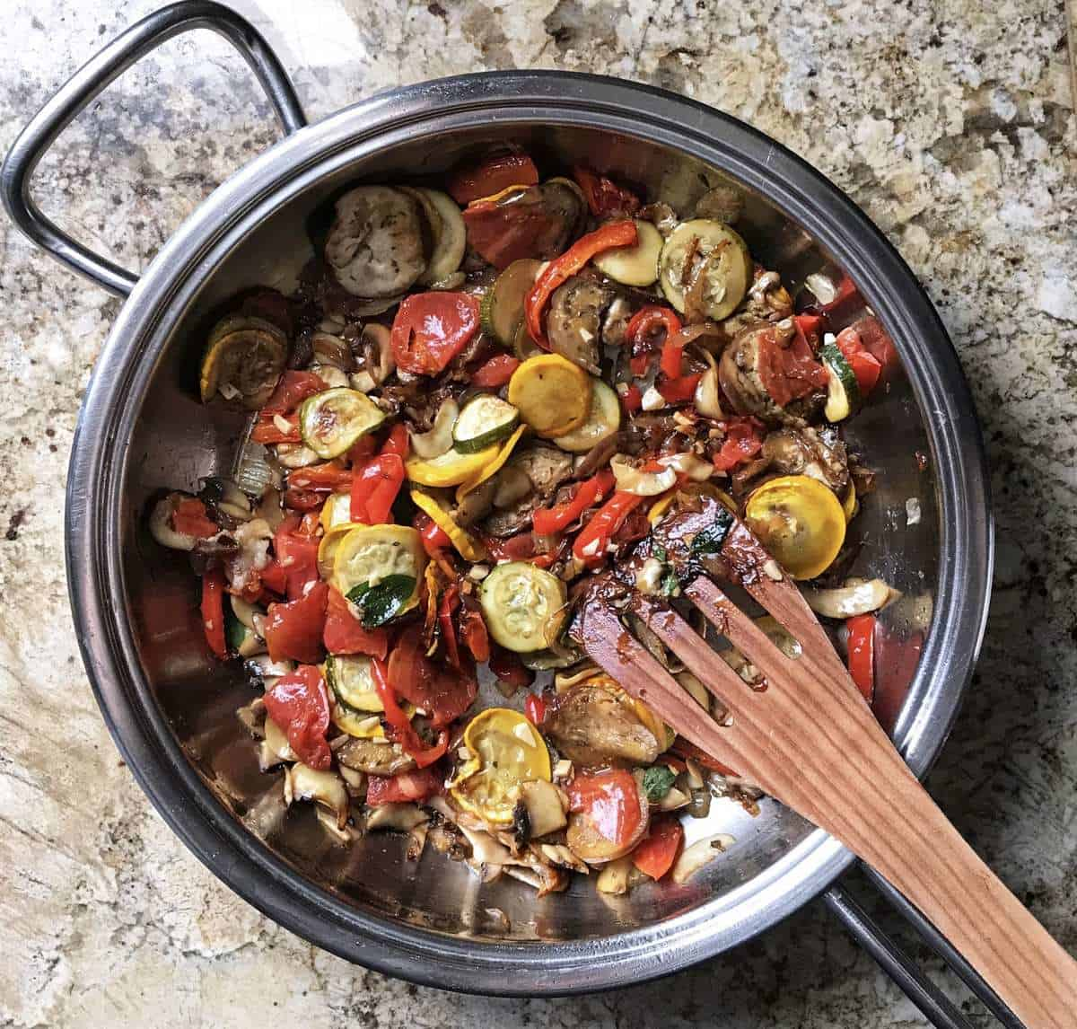 The addition of grilled vegetables to the pan of sauteed shallots and mushrooms.
