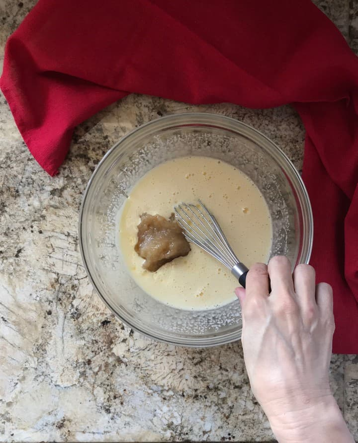 Homemade applesauce is being added to the wet ingredients of the apple cake.