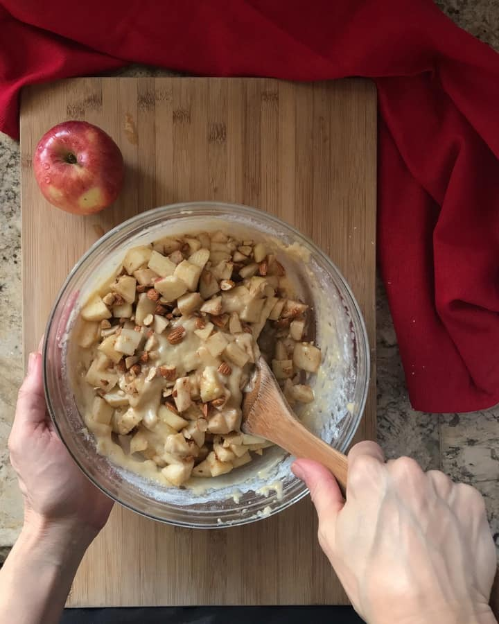 The diced apples are being combined with the batter of the apple cake.