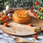 Roasted Cherry Tomato Sauce in a jar, surrounded by fresh garlic, fresh cherry tomatoes and dried oregano.