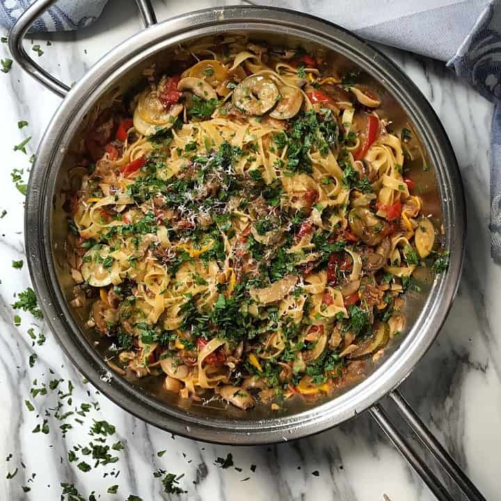 An overhead shot of the grilled vegetable pasta in the pan, with minced parsley scattered about.