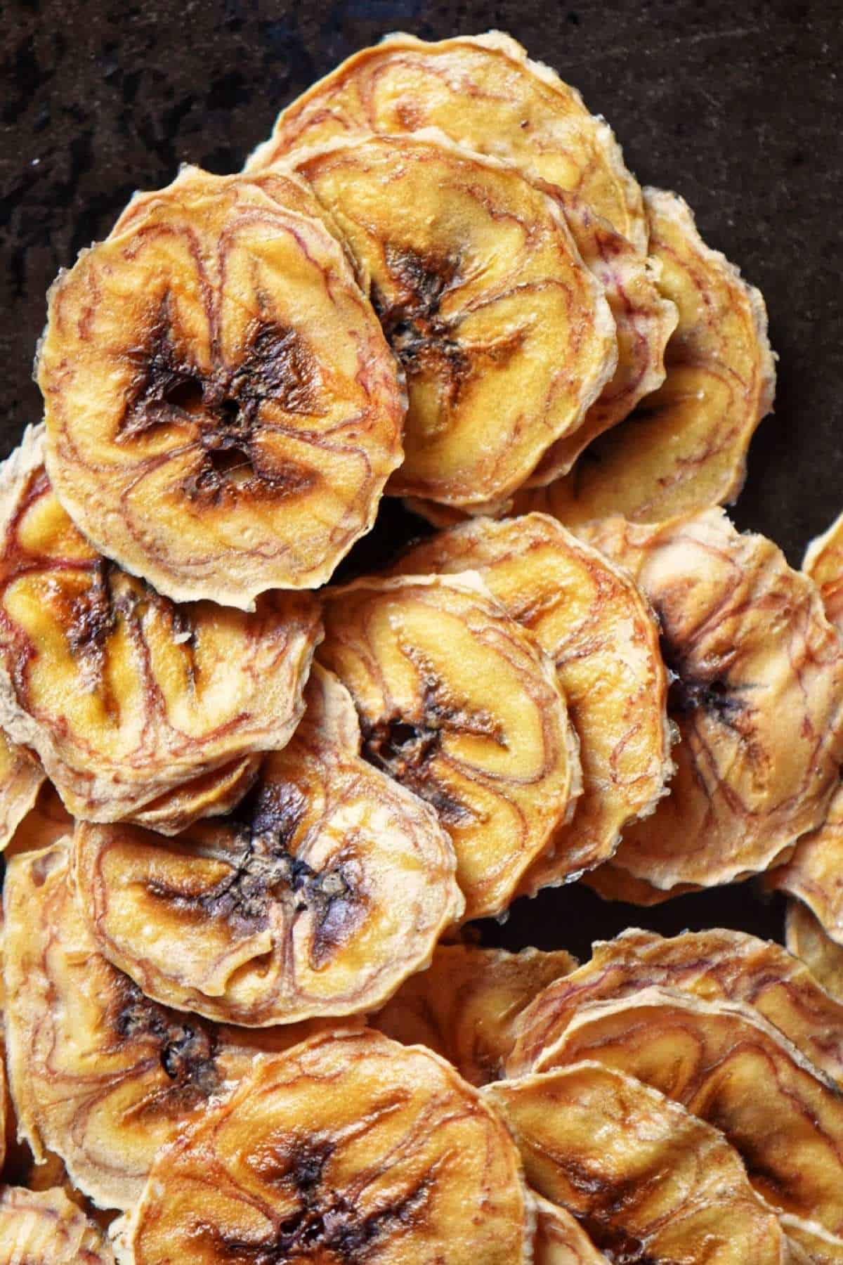 Thinly sliced homemade banana chips piled up high placed on a dark platter.