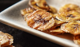 Baked banana chips placed on a white serving dish.
