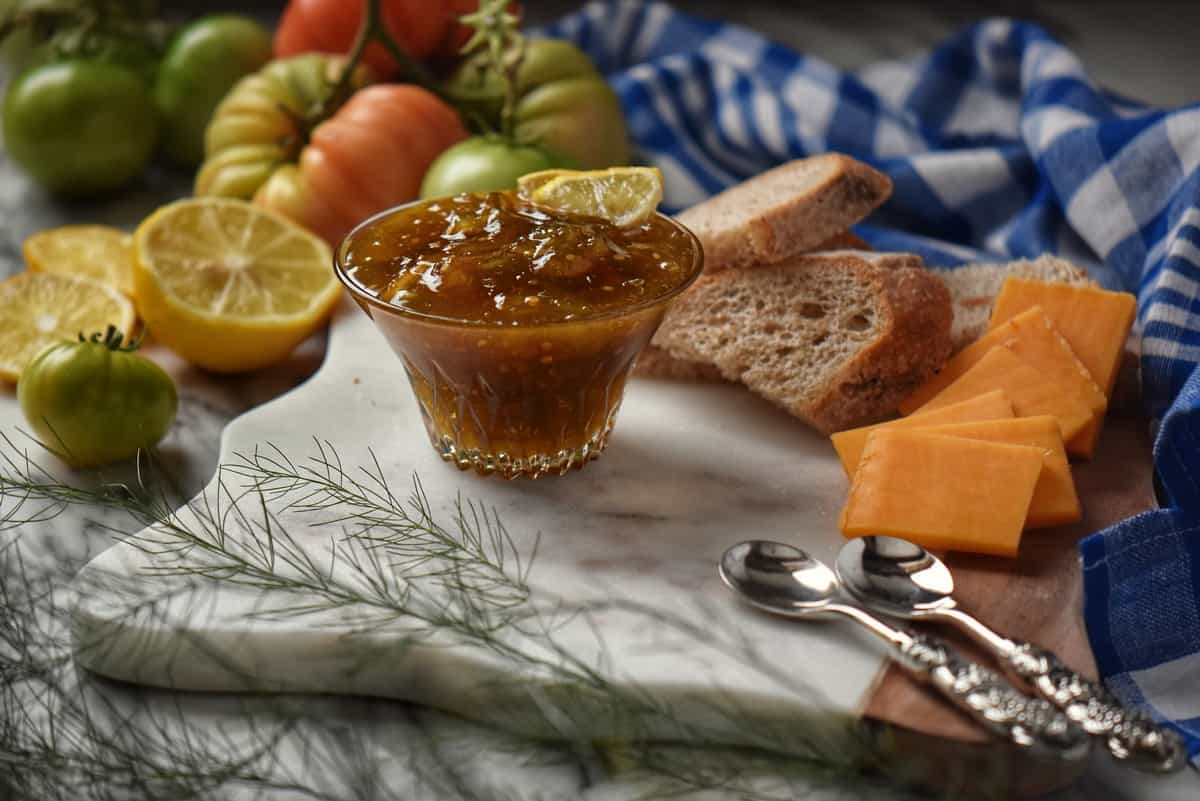 A bowl of green tomato preserves on a marble cheese board surrounded by unripe green tomatoes and lemons.