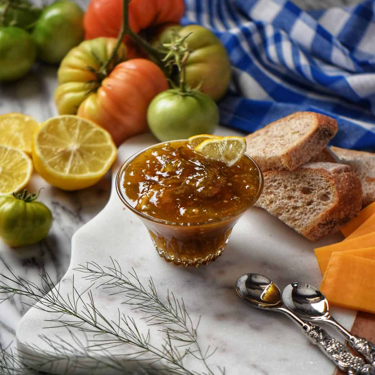 Green tomato jam is in a glass bowl, surrounded by fresh lemons, green tomatoes, and cheese.