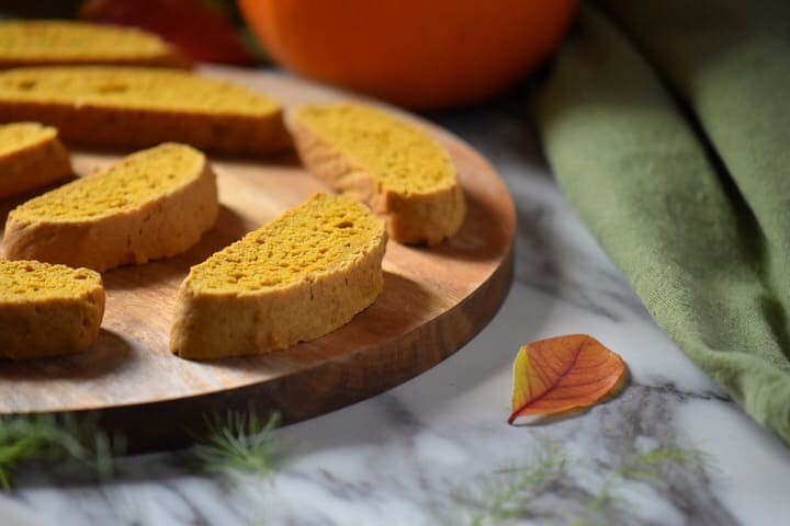 A few fall cookies, specifically pumpkin biscotti, on a wooden serving board.