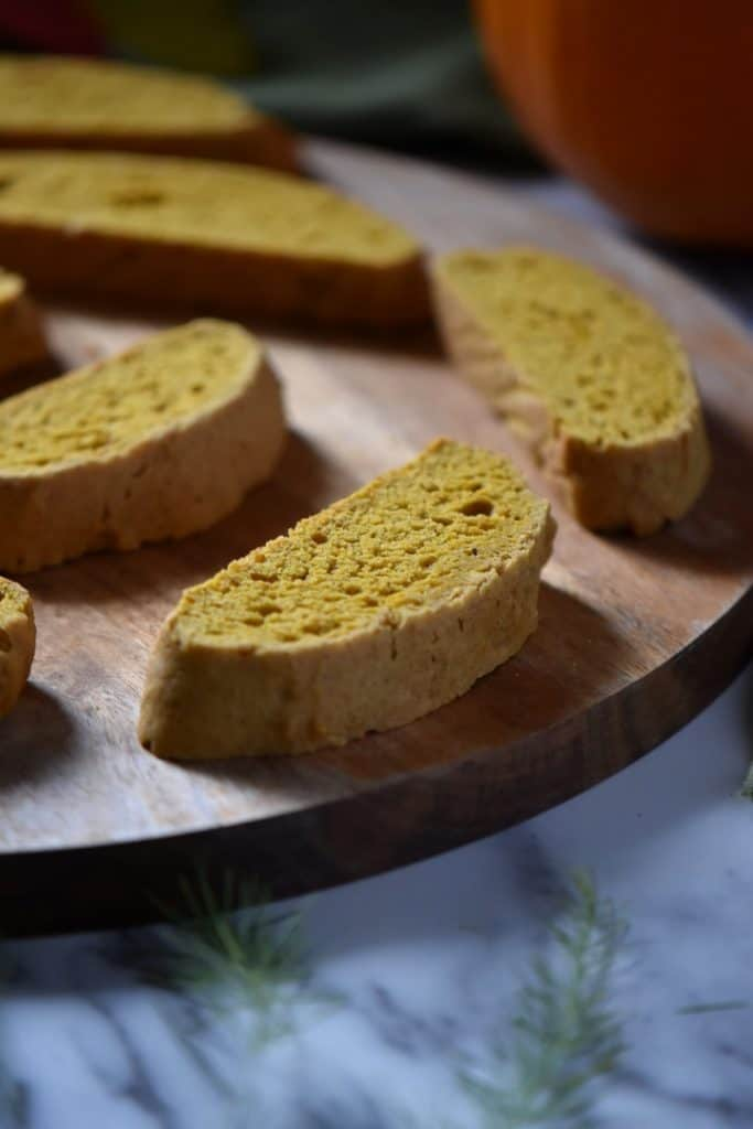 A close up of a few pumpkin biscotti on a wooden serving board.