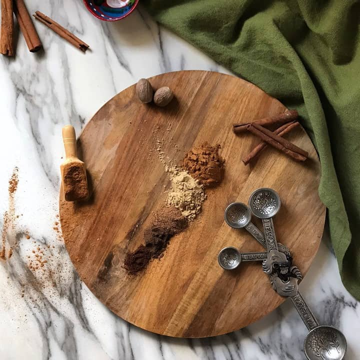 An overhead photo of ground spices like nutmeg, cinnamon and cloves on a wooden board.