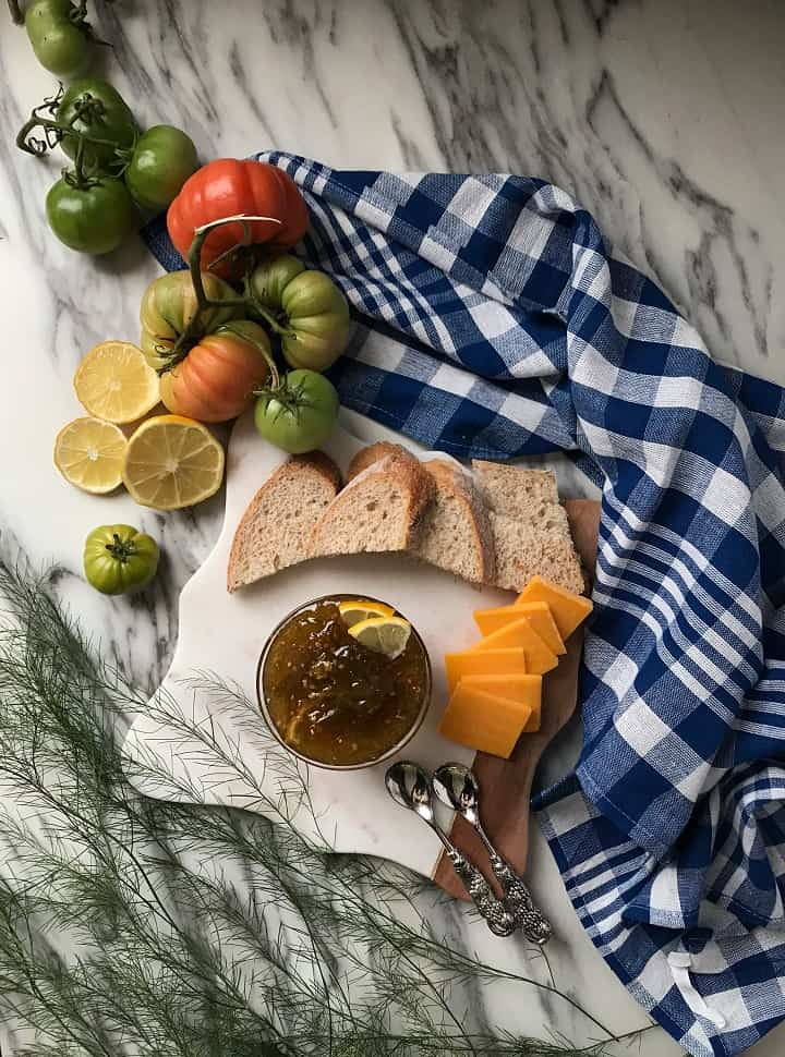 An overhead shot of a small cheeseboard with a bowl of tomato preserves, bread, cheese and a checkered blue tea towel.