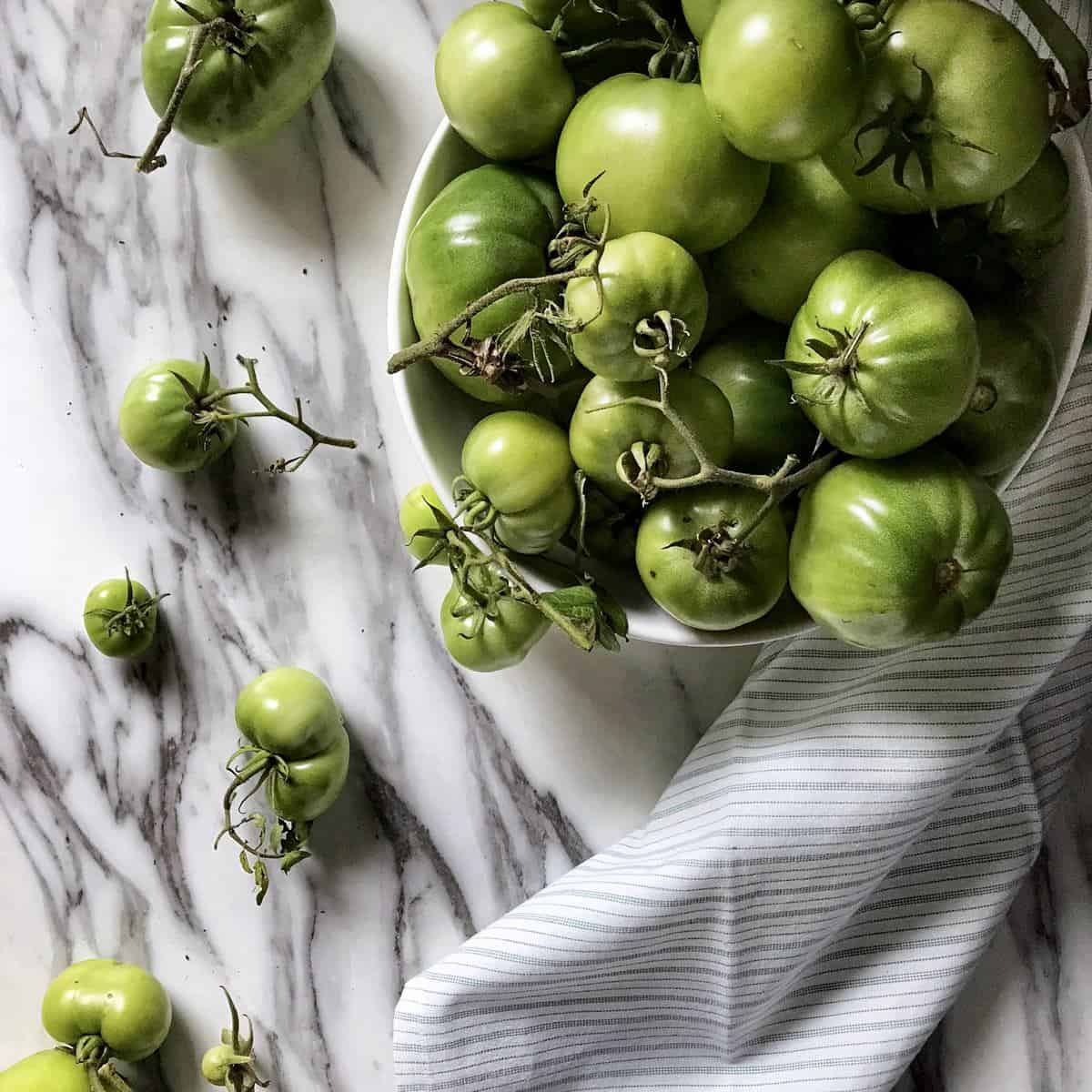 Green tomatoes in a bowl and on a counter.