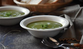 Two bowls of Cream of Broccoli soup with a few tablespoons in the foreground.