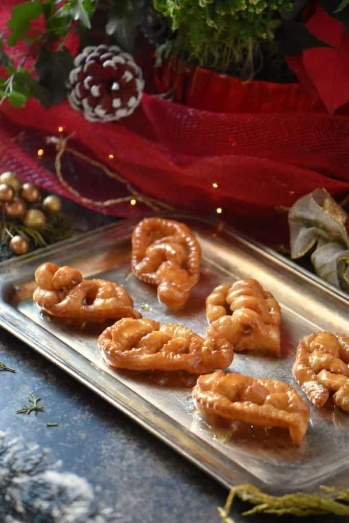 A tray of Caragnoli, an Italian Christmas cookie, on a silver platter.