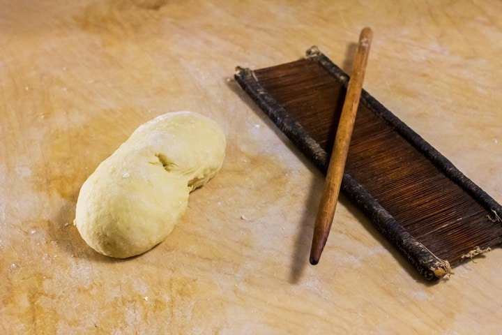 "A ball of dough and an original board and rod, called ""petene"" and ""fuso"" to make caragnoli."