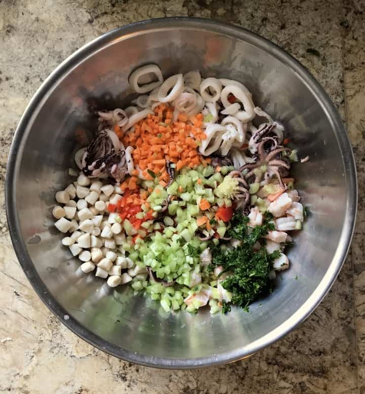 The ingredients to make the seafood salad are combined in a large bowl.