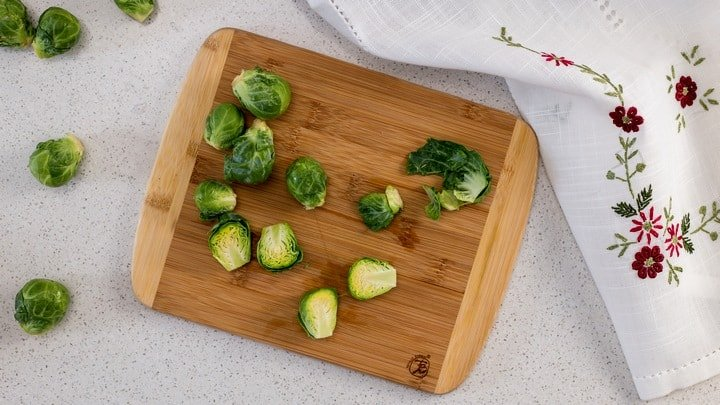 An overhead shot of halved Brussels sprouts on a wooden cutting board. They are one of the best oven roasted vegetables.