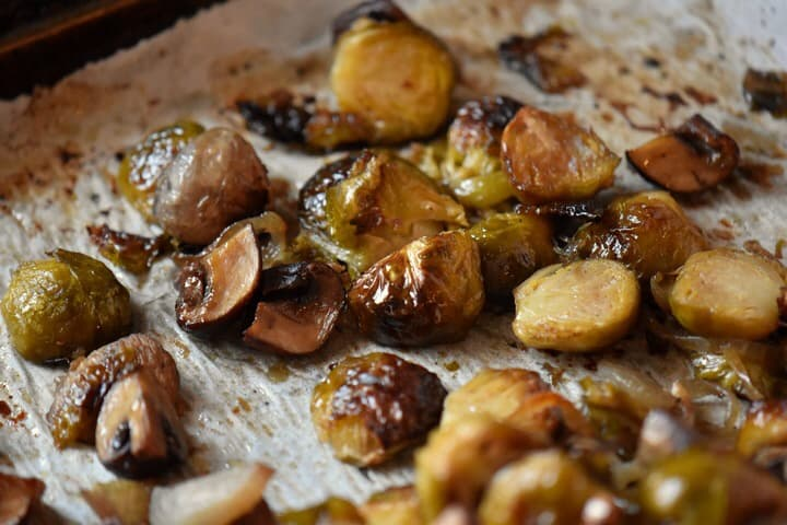 A close up shot of caramelized Brussel sprouts on a parchment lined baking sheet.