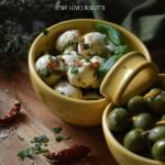 Marinated Mozzarella balls in a yellow ceramic dish make the perfect appetizer.