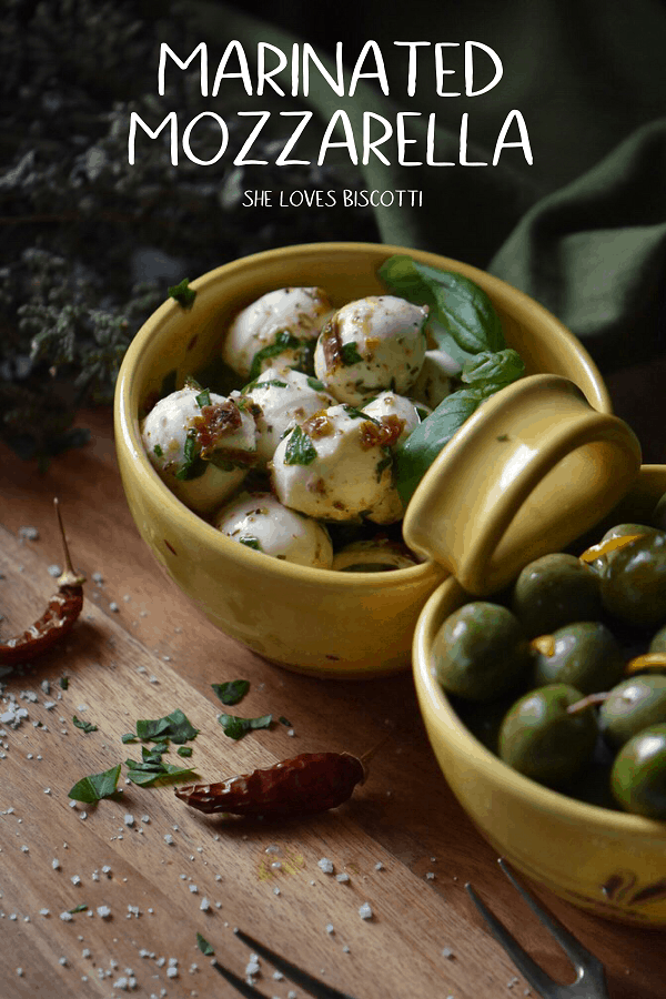 Marinated Mozzarella balls in a yellow ceramic dish make the perfect appetizer.