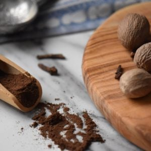 The final product of this allspice recipe can be seen scattered next to a wooden board.
