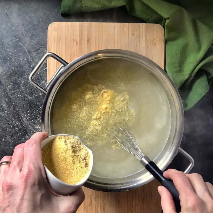 Polenta is slowly being poured in a pot of boiling water, ready to be whisked.