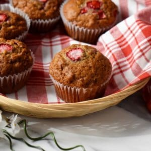 Strawberry muffins placed on a checkered red tea towel, in a wicker basket.
