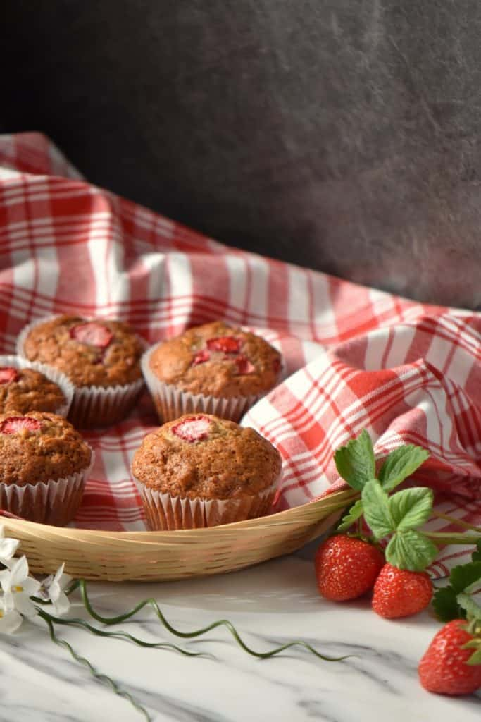 Fresh strawberries surround a wicker basket full of strawberry muffins.