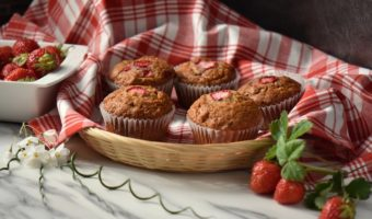 A wicker basket lined with a checkered red tea towel, filled with strawberry muffins.