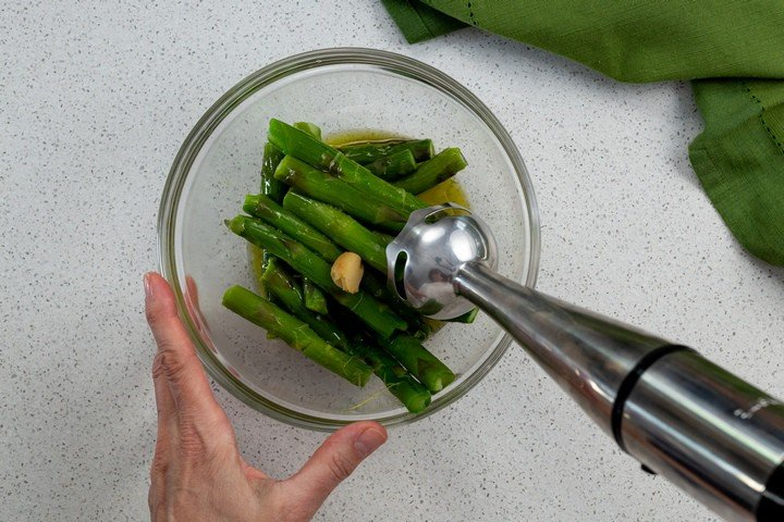 A hand held blender about to puree asparagus, olive oil, lemon juice and one roasted garlic clove together.