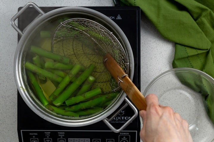 Asparagus stalks are being removed from a pot of boiling water.
