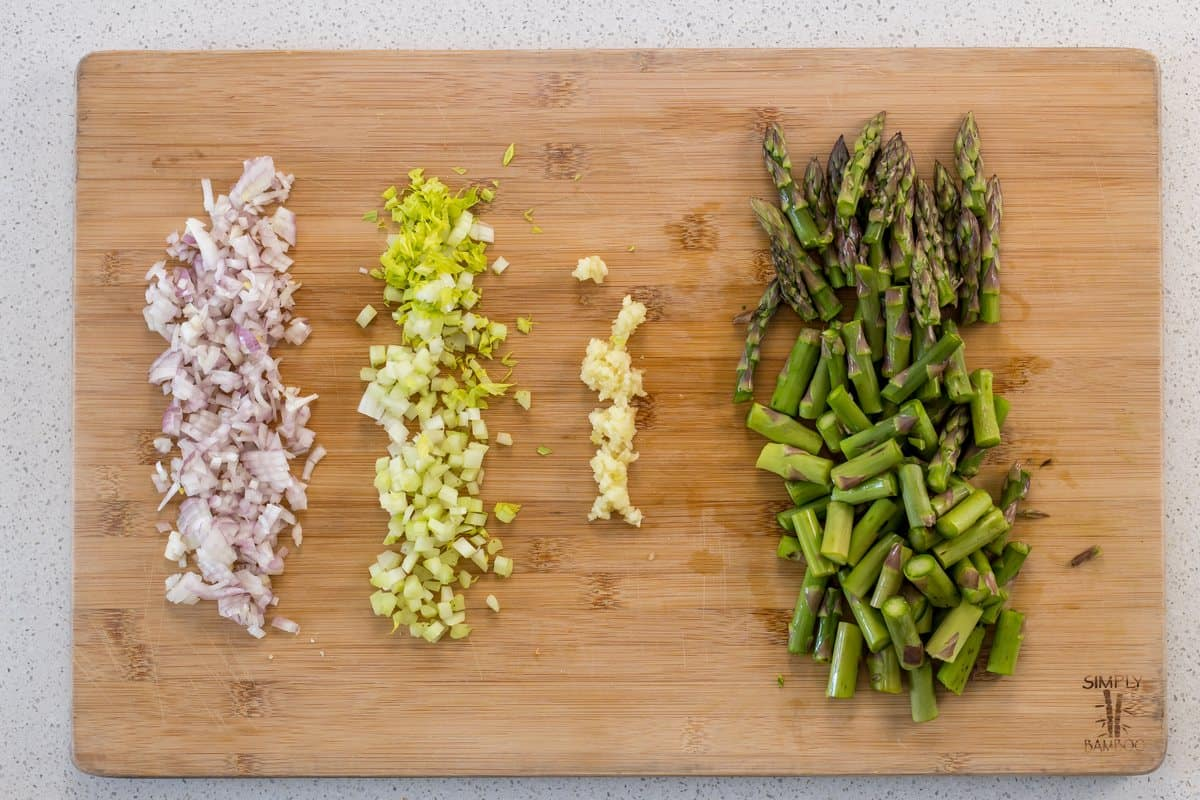 Chopped shallots, celery , garlic and asparagus on a wooden board.