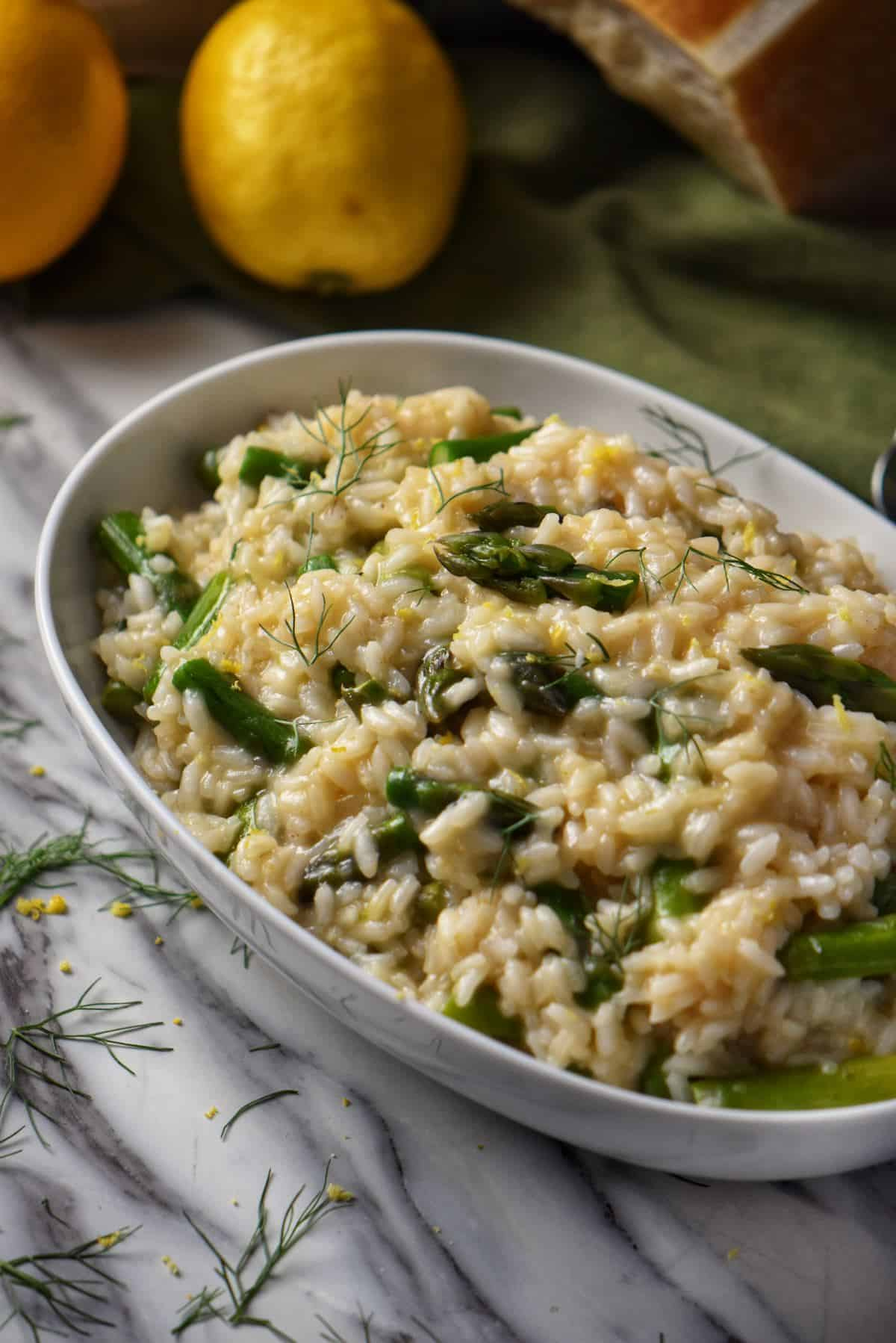 A white oval bowl is filled with creamy asparagus risotto. In the background. a lemon and a block of Parmesan cheese are visible.