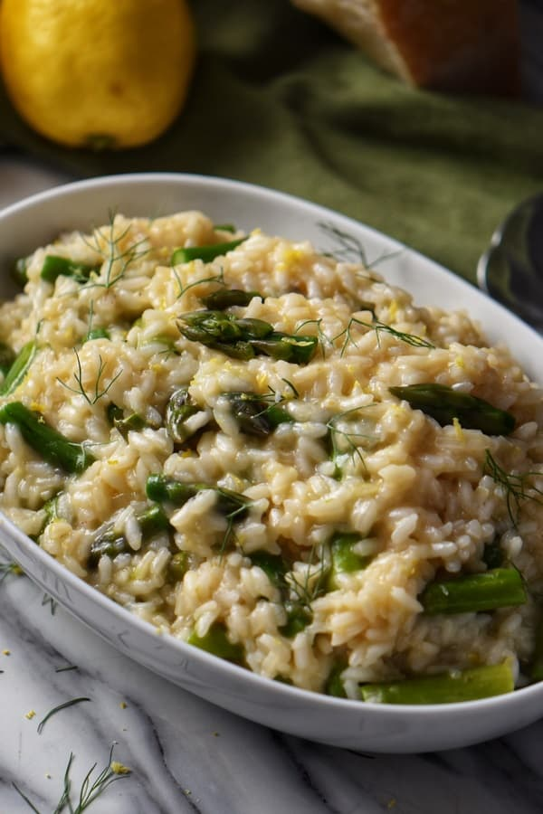 Creamy asparagus risotto garnished with lemon zest and fennel fronds in a white oval serving dish.