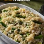 Asparagus risotto in a white oval dish, garnished with fennel fronds.