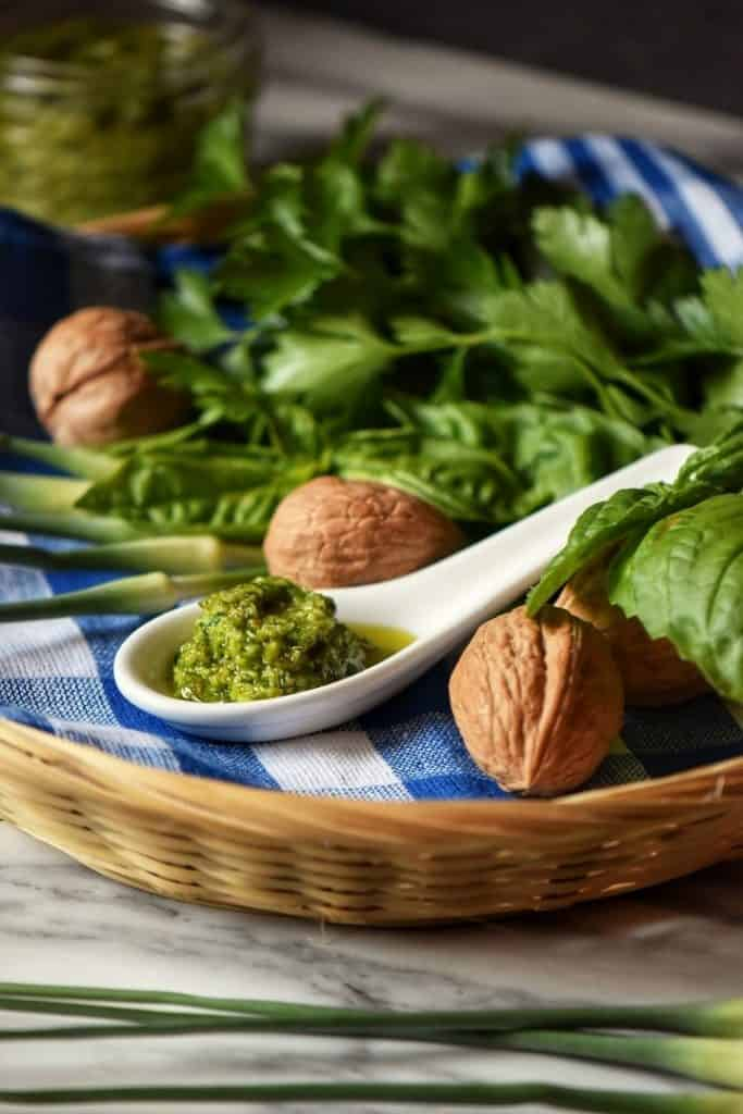 One tablespoon of Garlic Scape Pesto placed in a wicker basket along side walnuts, basil and parsley.